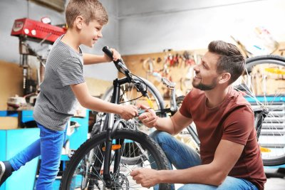 father and son working on bicycle in their garage